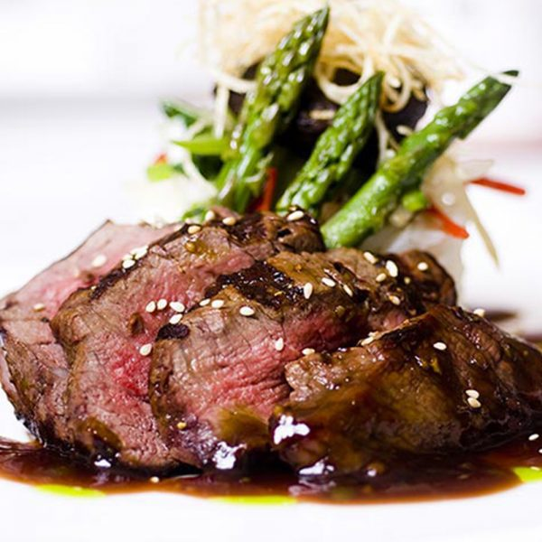 A plate of finely cooked and slice steak with asparagus